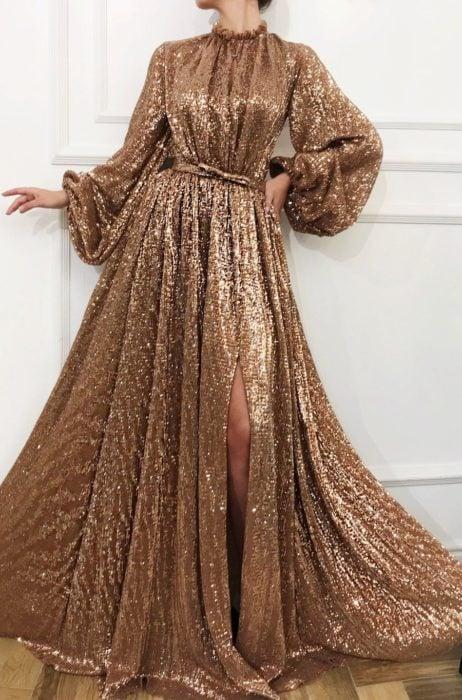 Mujer con vestido de princesa, sin escote, con mangas y abertura en la pierna, color dorado con glitter