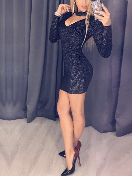 Mujer rubia tomándose una selfie frente al espejo con un vestido con mangas de color negro con brillos