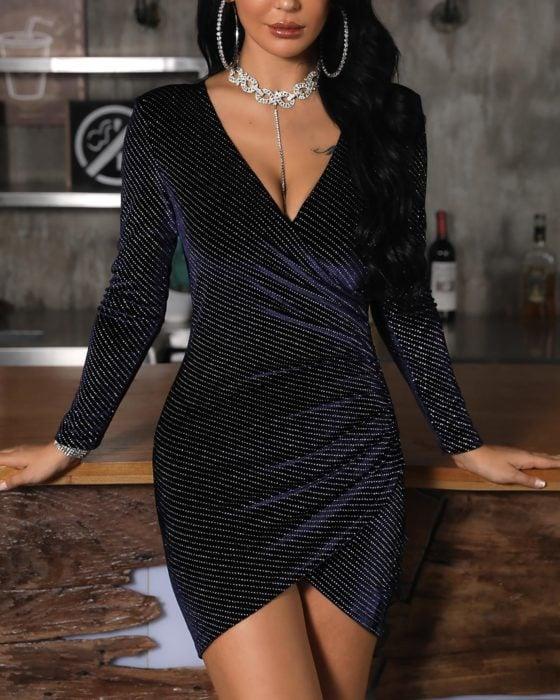 Mujer de cabello oscuro con un vestido negro con líneas blancas de brillos