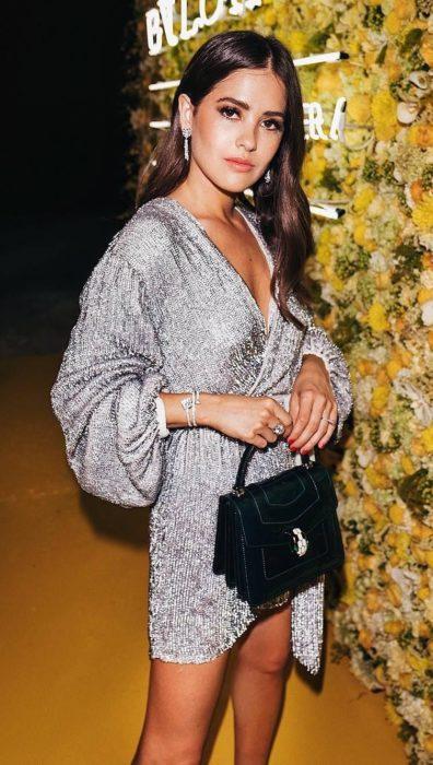 Mujer de cabello castaño con vestido con mangas holgadas color plateado brillante