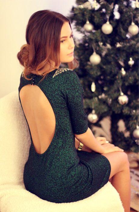 Mujer con peinado de chingo despeinado sentada frente a un árbol de Navidad con vestido verde, brillante, sin espalda