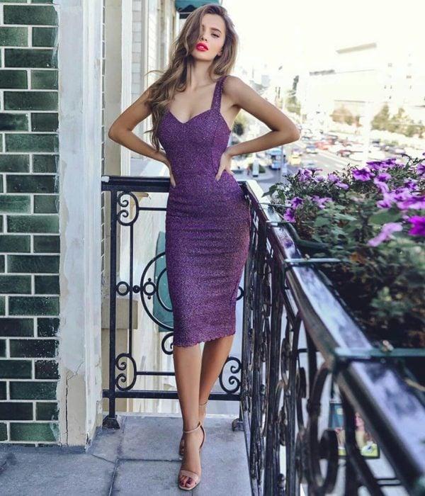 Mujer rubia en un balcón, con vestido morado brillante, ceñido al cuerpo y sin mangas