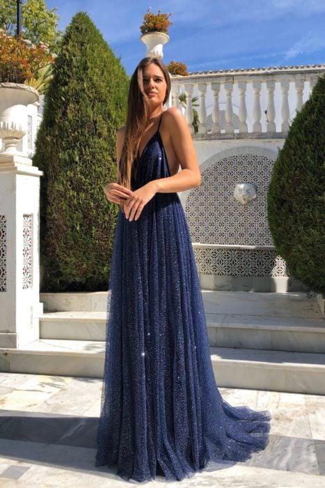 Mujer de cabello castaño largo y lacio, frente a una fuente con vestido largo de tirantes azul con brillos