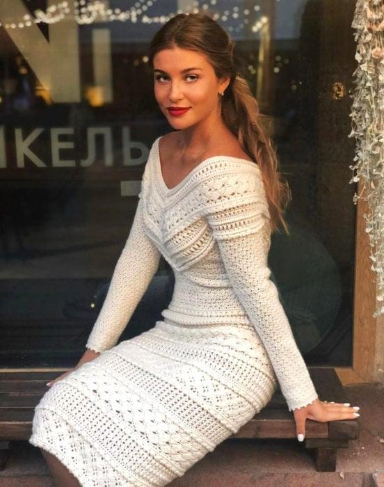 Chica rubia con peinado de cola de caballo con un vestido tejido blanco