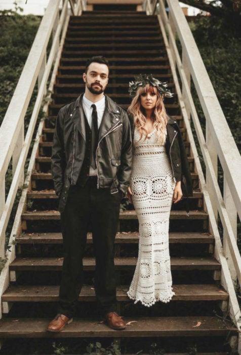 Sesión de fotos de pareja de recién casados en una escalera, hombre con traje y chamarra de cuero negro, mujer con cabello rubio y suelto, con corona de flores, vestido de novia blanco, largo y tejido con chamarra