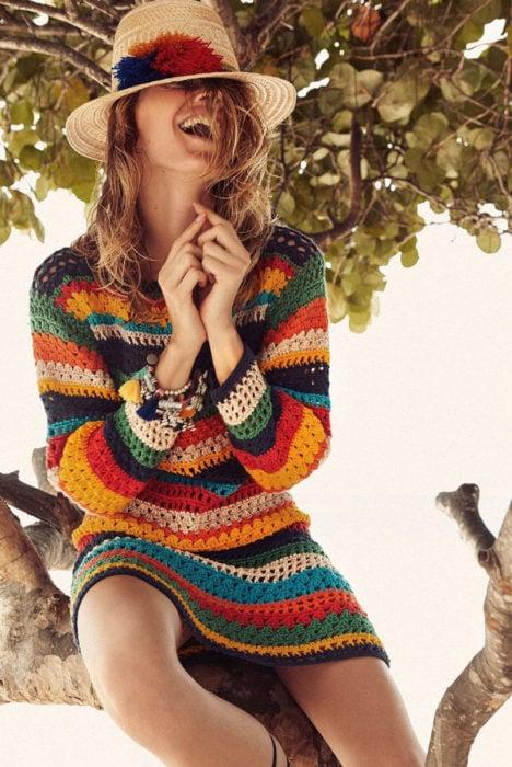 Mujer riéndose, con sombrero y vestido de colores tejido
