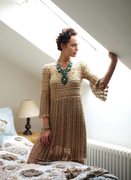Chica en recámara con peinado estilo Frida Kahlo con collar grande de flores verdes con vestido tejido beige
