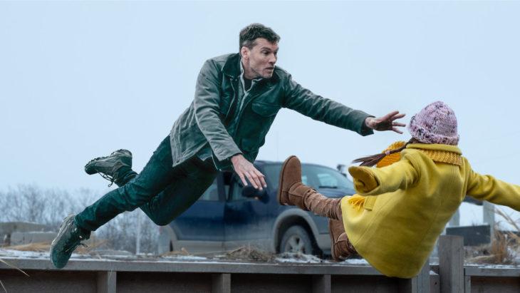 Escena de la película Fractured de Netflix. Niña cayendo al agua mientras su papá trata de salvarla