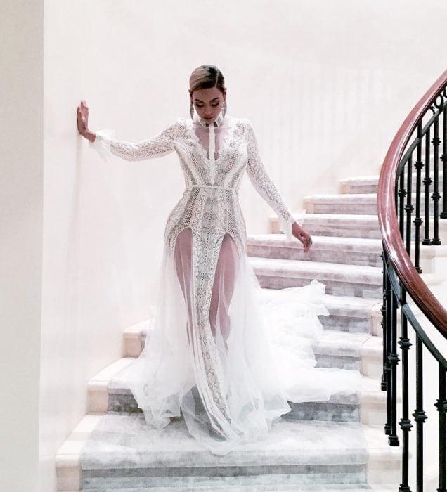 Beyonce bajando las escaleras mientras usa un vestido blanco para ir a un evento