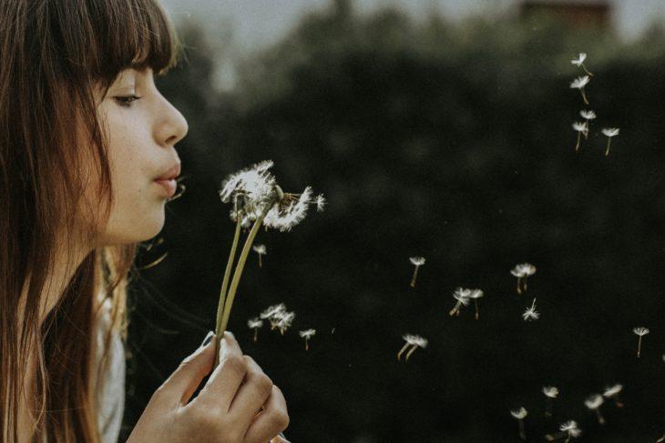 Mujer soplándole a una flor