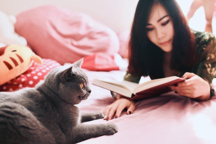Mujer leyendo un libro y su gato junto a ella
