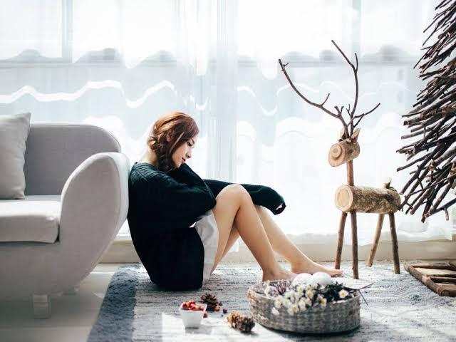 Chica sentada sola frente al árbol de Navidad