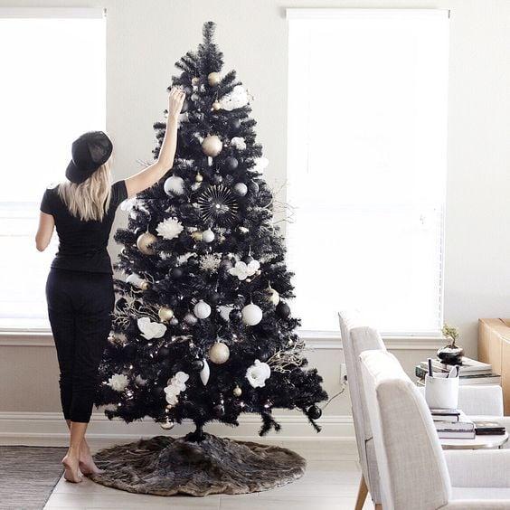 Chica decorando pino navideño con esferas blancas