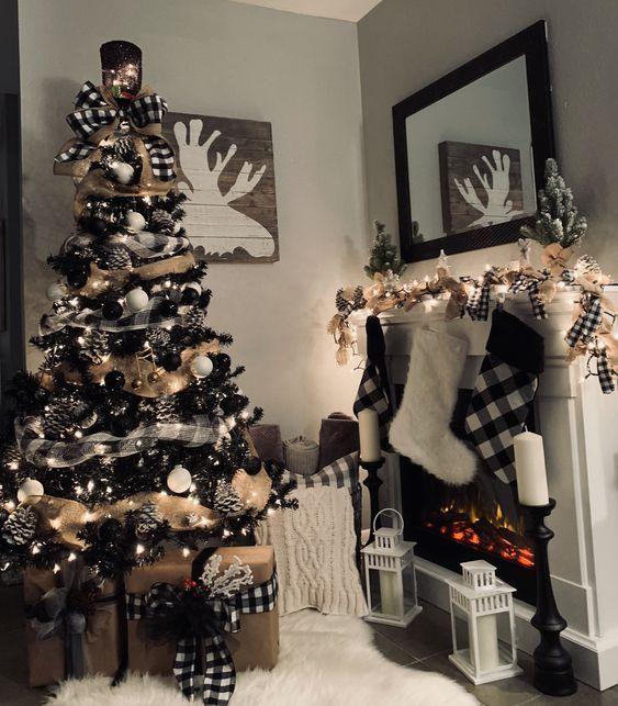 Pino navideño en color negro al lado de la chimenea blanca