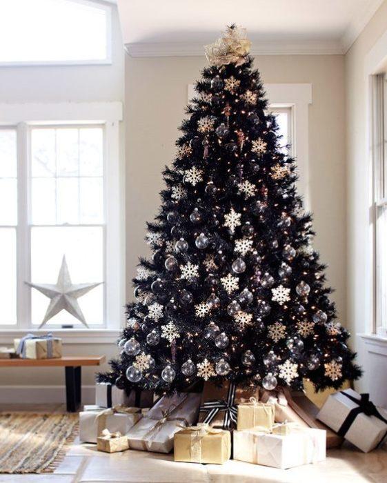 Pino navideño en negro con regalos en dorado alrededor