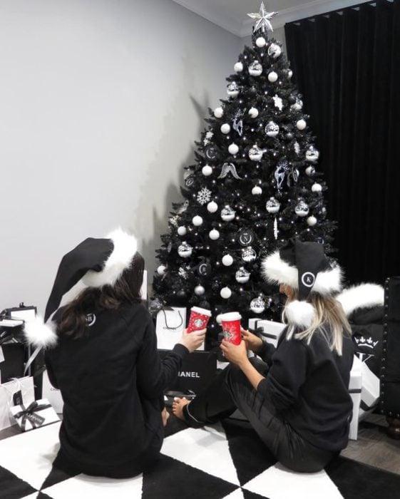 Chicas sentadas al pie del pino navideño en color negro