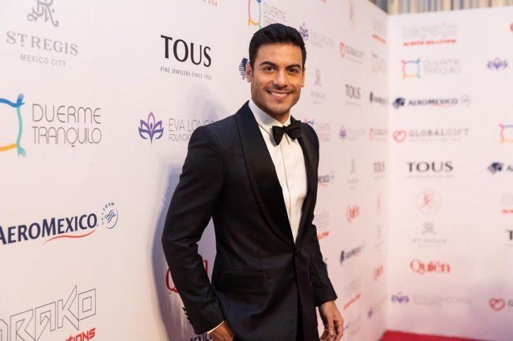 Carlos Rivera posando para una foto en la alfombra roja de la gala global fift
