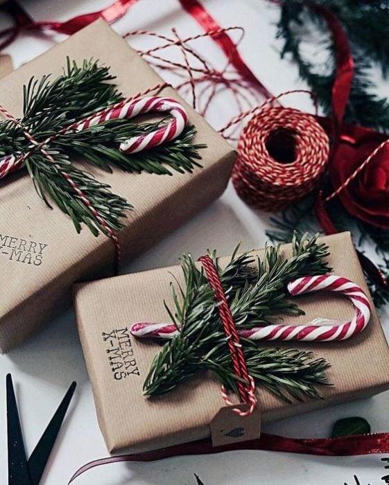 Caja de cartón decorada con hierbas navideñas y caramelos de bastón