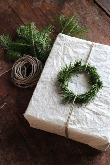 Caja forrada con papel y una mini corona de hierbas