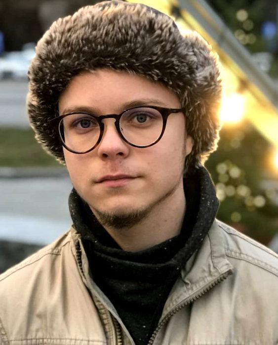 Finlandia te paga por tener bebés; guapo chico finlandés de ojos grises, con lentes y gorro peludo