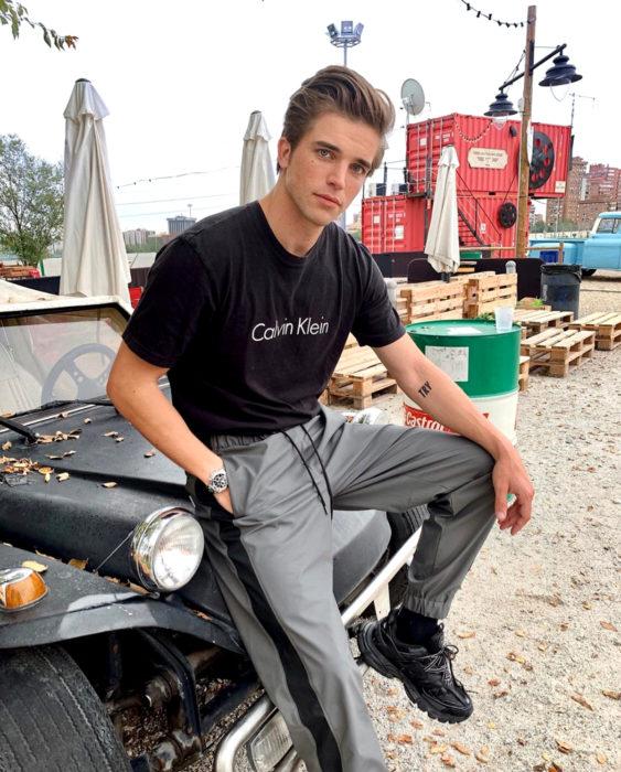 Finlandia te paga por tener bebés; guapo chico finlandés sentado en un Jeep, con playera de Calvin Klein, pants grises y tenis Fila