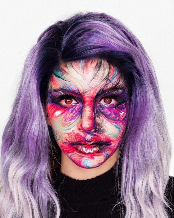 Chica con un maquillaje de varios colores y cabellera de color morada
