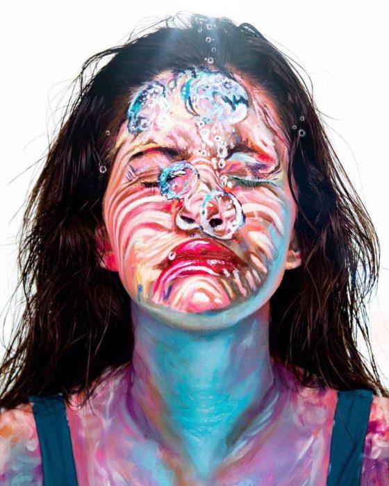 Chica con el rostro pintado con colores que simulan estar debajo del agua