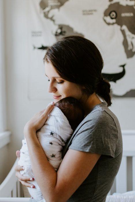 Mujer cargando entre sus brazos a un bebé recién nacido