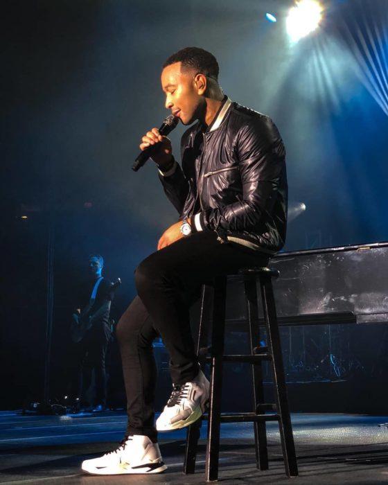 John Legend cantando en un concierto mientras está sentado en un banco