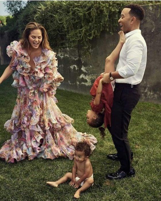 Familia de Chrissy Teigen y John Legend jugando en el pasto de su casa