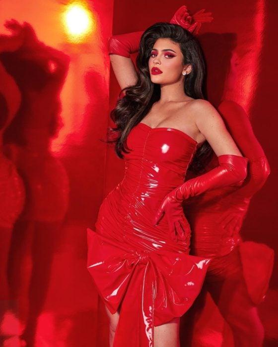 Kylie Jenner recargada en un estante mientras usa un vestido de color rojo