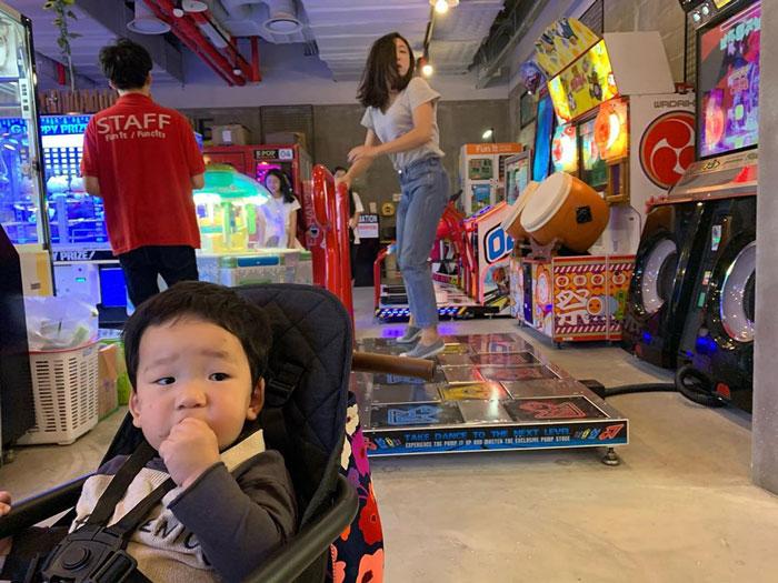 Mamá jugando videojuegos mientras su hijo la observa