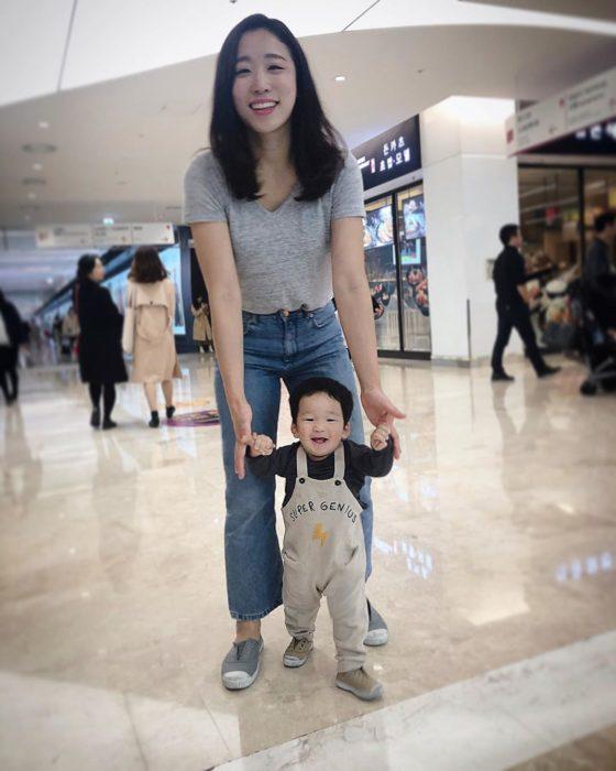 Mamá ayudando a su hijo a caminar mientras están en un centro comercial