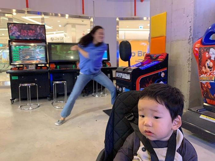 Mamá jugando con una maquina mientras su hijo la observa desde la carreola