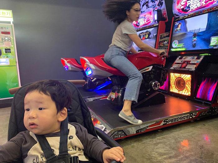 Mamá arriba de una moto de videojuegos mientras su hijo la observa