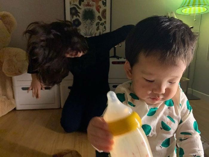 Mujer bailando detrás de su hijo mientras ambos están en la habitación