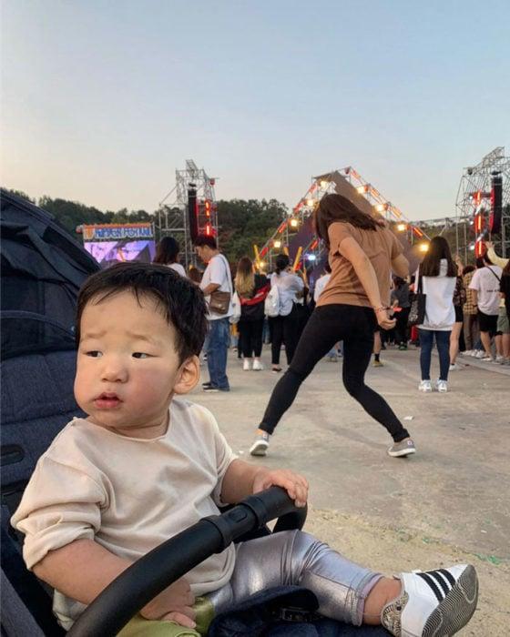 Mamá bailando en un festival mientras su hijo la observa desde la carreola