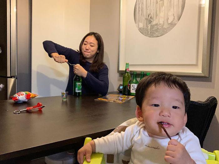 Mamá abriendo una botella mientras su hijo está frente ella en la silla