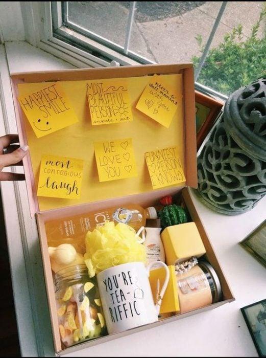Caja de regalo rellena con una taza y post-it amarillos