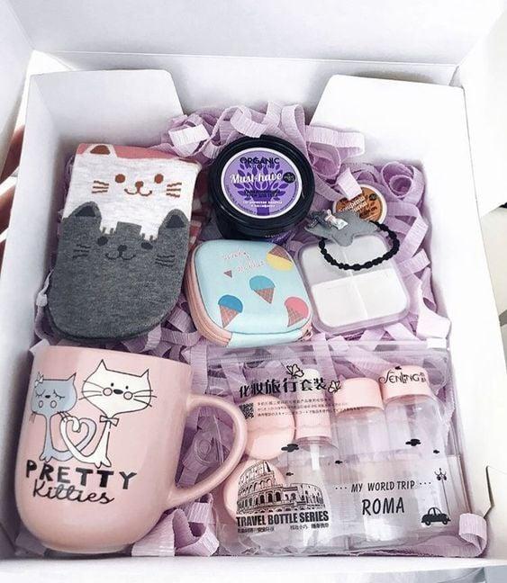 Caja de regalos rellena con una taza y accesorios de minino