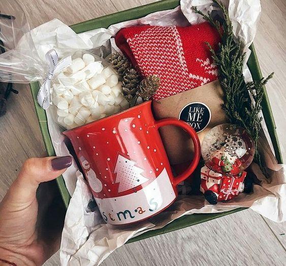 Caja de cartón rellena de bombones una taza y un bolsa de café