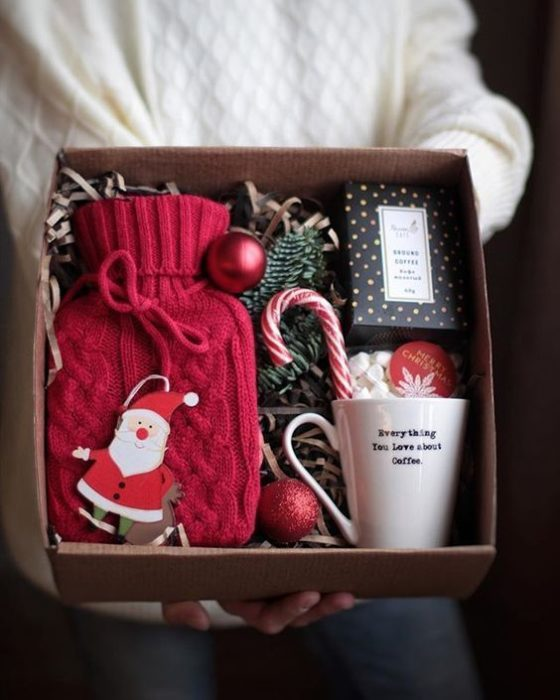 Caja de regalo rellena con guantes de estambre, una taza y caramelos