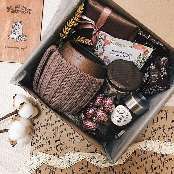 Caja de cartón rellena con una taza , chocolates y un porta vaso de estambre