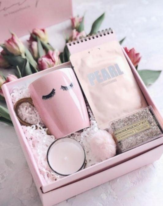 Caja de regalo rellena con una taza rosa, velas y una agenda