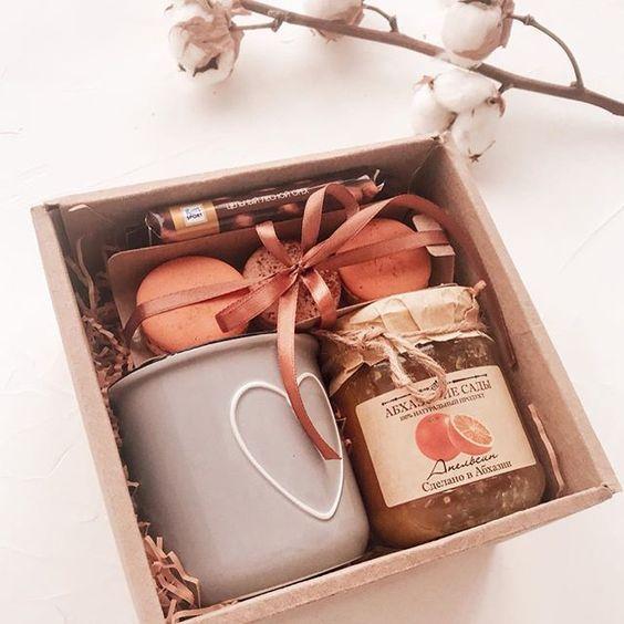 Caja de cartón rellena de una taza y mermelada de naranja