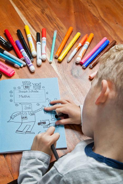 Joel niño pintando con diferentes colores las hojas de sus libretas