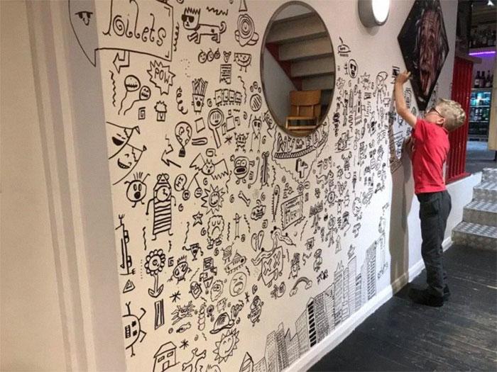 Niño dibujando la pared de un restaurante con diferentes dibujos