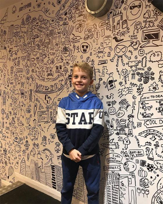 Niño frente a una serie de dibujos que hoz en un restaurante