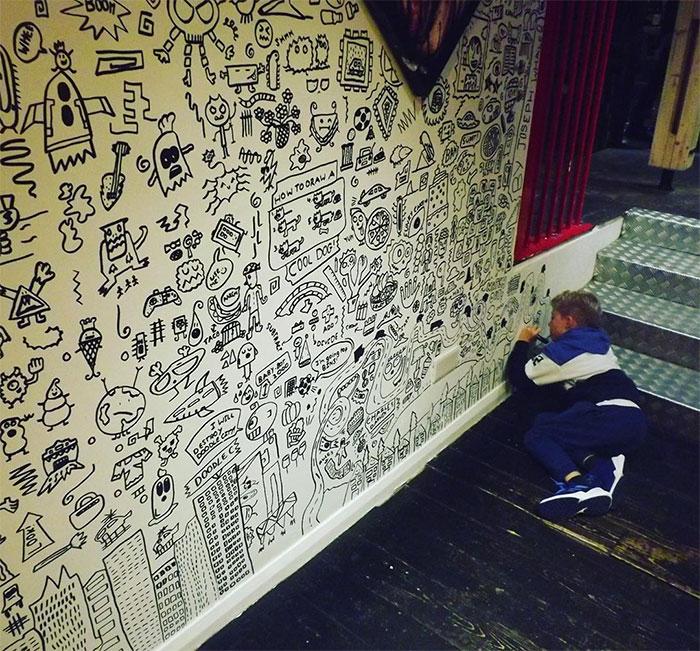 Niño dibujando la pared de un restaurante con diferentes garabatos