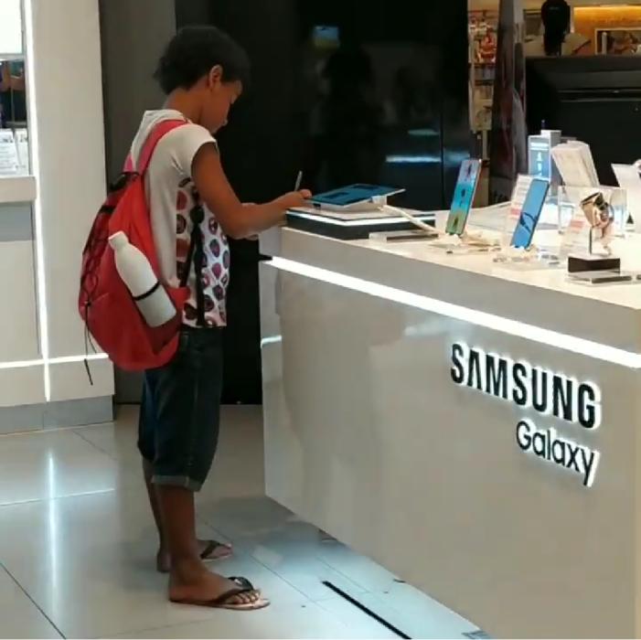Niño hace tarea en una tienda de celulares porque no tiene Tablet